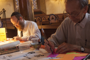 A Jewish scribe and Chinese calligrapher work side by side at the Egg Rolls and Egg Creams Festival.
